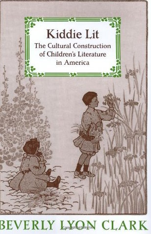 Cover of Kiddie Lit: The Cultural Construction of Children's Literature in America, by Beverly Lyon Clark. A sepia-toned image of two children in a field of tall grasses and flowers. The child on the left, sitting with their legs straight, has shoulder-length hair and is wearing a puffy dress with long sleeves and tall dark boots. The other child, on the right, is standing, touching one of the tall flowers. This child has very short hair and is wearing a long-sleeved top that reaches almost to the knees and flares out over a pair of bloomers. The child has shin-length dark socks and light-colored saddle shoes.