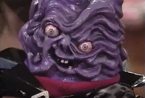 Close-up of the Slime Monster's wrinkly purple head, with bulging, bloodshot eyes.