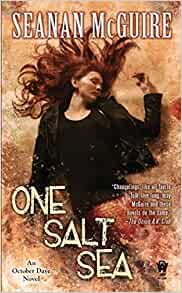Cover of One Salt Sea, by Seanan McGuire. A woman with tanned skin and long, dark red hair is lying on the sand. She is wearing a black t-shirt and black leather jacket, and she has a goldfish-orange fish tail.