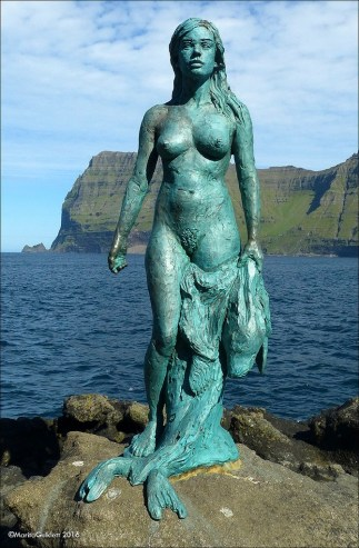 Bronze statue of a naked woman holding a seal pelt. The statue has turned green from the sea air. It stands on a rocky island, with the sea and a cliff in the background.