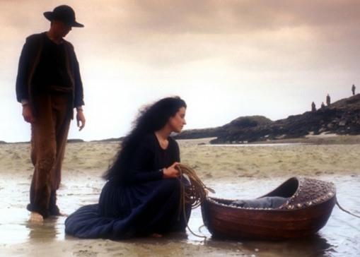 Image from the movie The Secret of Roan Inish. A silhouetted man with a broad-rimmed hat stands in the shallow water at the edge of the shore. In front of him kneels a woman with dark hair that flows down to her lower back. The woman holds a coiled rope in one hand and rocks a wooden cradle in the other.