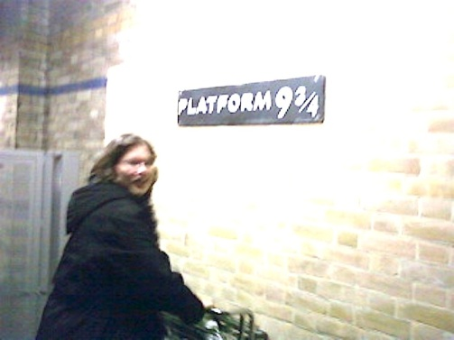 A blurry photo of a woman with shoulder-length dark hair in a black winter coat pushing a quarter of a shopping cart into a brick wall. Above her is a sign that says Platform nine and three quarters.