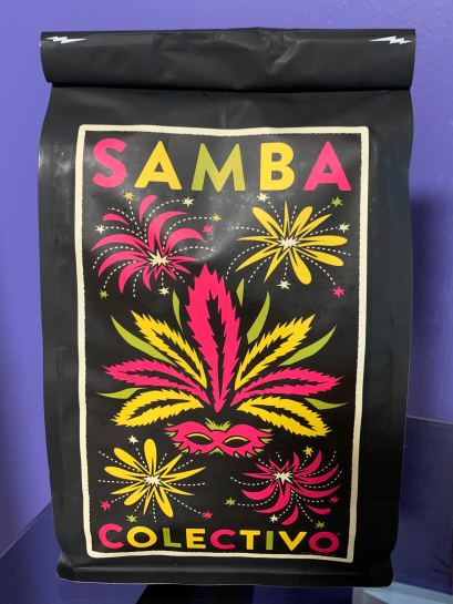 A bag of Samba coffee, by Colectivo Coffee Roasters. The bag is black, with a Mardi Gras design, including pink and yellow fireworks and a pink Venetian mask with giant pink and yellow feathers.