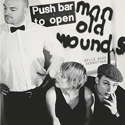 Cover of Push Barman to Open Old Wounds album. A man stands on the left side, looking off to the left, wearing a long-sleeved white dress shirt and black pants, with a black bow tie. He has his black-gloved hands on his hips. A young woman with short blond hair sits to the right of him, looking up at him. She wears a sleeveless black dress. A young man in a chapeau sits to the right of her, staring at the viewer with his left hand touching his face.