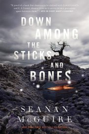 Cover of Down Among the Sticks and Bones. Dead grey hills rise up against a cloudy, grey sky. A blackened tree stands on the middle hilltop and a treasure chest sits in the slight valley formed by the three hills. A golden-orange glow comes from the slightly opened trunk.