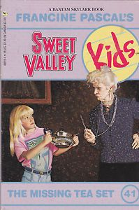 "Cover of Sweet Valley Kids 41: The Missing Tea Set.  This one has the more typical series logo, with the words ""Sweet Valley"" in college pennant font, and the word Kids drawn in a childlike font over a yellow circle with blue lines, like a piece of writing paper.  The i has a heart over it.  The background is lavender.  In the middle is a scene: a girl with long blond hair holds out a large metal teapot with both hands.  She's wearing a bright pink t-shirt with an abstract blue and green design in the middle, and blue jeans.  She looks scared.  She's looking at an older, cranky-looking lady with her white hair piled into a loose bun on top of her head.  The lady is wearing a dark blue sweater over a black skirt or pants, and a pearl necklace.  She's holding what looks like a short wand or pen and shaking it at the girl."