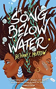 Cover of A Song Below Water, by Bethany C. Morrow.  Two teenage girls stand back to back, close enough to lean against each other.  Their long hair, in twists and coils, floats upward -- the background is light blue, with a few bubbles floating up with the girls' hair.  The girl on the left has light blue eyeshadow and a light blue earring that looks like a chandelier.  The girl on the right also has blue eyeshadow, with a small gold hoop earring and a streak of blue scales and glitter on her cheek.  Both girls have light gray-green seaweed woven into their hair.