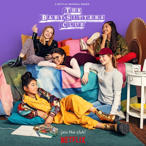 "The Babysitters Club Netflix poster. Five girls cluster around a bed with an old patchwork cover. Three girls lounge on top of the bed: Stacey, on the left, has pale skin and shoulder-length blond hair; Mary-Anne, lying on her stomach, has light brown skin, dark hair in two braids, and black-rimmed glasses; Dawn, on the left, has tanned skin and long black hair. Two girls lounge on the floor: Kristy, on the right, just under Dawn, is kneeling with her right arm resting on the bed. She has pale skin and brown hair in a pony-tail, under a dark red baseball cap. Claudia lies on her back, staring up at Mary-Anne and Dawn. She has light skin and black hair pulled up into a messy bun on top of her head. She's wearing a jellow jumpsuit under a patchwork jacket, and gold high-top boots (can you tell she's the artist?) The wall behind them is purple, with the babysitters Club logo in its classic toy block style, above and between Stacey and Dawn's heads. The tag line at the bottom of the poster, just above the Netflix logo, reads: ""Join the club!"""