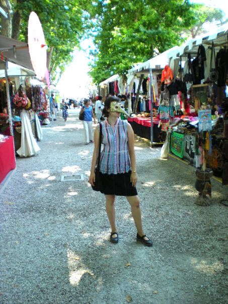 Photo of myself, a woman with short dark hair and a Venetian Carnival mask (white and rectangular with a long, sharp beak) and a sleeveless top with multicolored vertical stripes. I'm standing in the middle of a market in Rome.