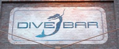 The Dive Bar sign, on the outside of the building. A dark blue-green silhouette of a vertical mermaid with one arm stretched upward and the other downward, with her hair flowing down along the latter arm. She's positioned between the words Dive Bar.