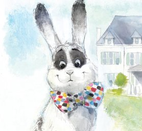 Close-up of the cover of John Oliver's Marlon Bundo book. You see a watercolor image of a smiling white rabbit with tall, perked-up ears that shift into grey towards the middle and black at the tips. He has a black standing-egg-shaped patch around each eye, and he's wearing a big bow-tie with a multicolored checkerboard pattern. He has a large grey patch over his tummy.