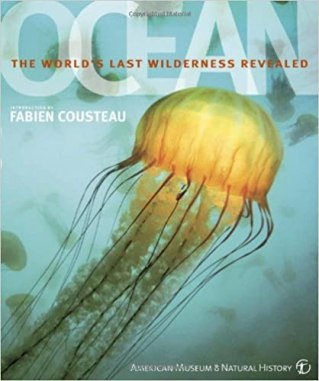 Cover of Ocean: the World's Last Wilderness Revealed, an American Museum of Natural History book written by Robert Dinwiddle and introduced by Fabien Cousteau. The background is a cerulean blue ocean with a few jellyfish silhouettes. In the foreground, you see a large, glowing yellow jellyfish. The title is written in large, translucent white letters just above the jellyfish, and the subtitle is in tiny red letters across the middle of the title.