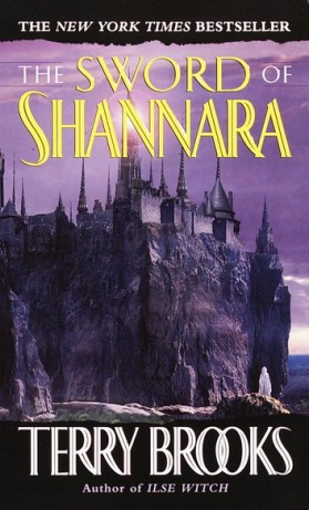 The purple cover of The Sword of Shannara, by Terry Brooks. The title is in yellow font at the top of the cover, while the author's name is in white at the bottom. In the middle, under a sky of various purple shades, you see a castle with many tall, sharp spires sitting on top of a cliff overlooking the sea. A white figure stands at the base of the cliff, in the bottom-right corner of the cover, just above the author's name.