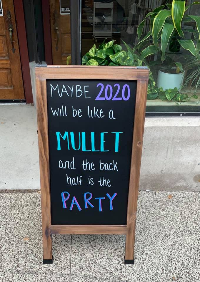 Outdoor black chalkboard that reads:  Maybe 2020 will be like a mullet and the back half is the party.  The words 2020 and party are in purple, while mullet is in turquoise.  The rest of the words are white.