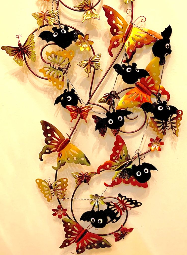 A garland of small puffball bats is woven around a wall hanging of metal butterflies, which are colored in red, orange, and yellow.