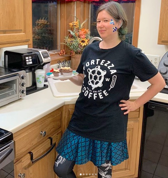 Photo of me, in my kitchen, wearing a black t-shirt with the words Fortezza Coffee making a circle around a large white turtle.  The letters F and W are on either side of the turtle, and a feather makes up each of the left and right sides of the circle.  Under the t-shirt, which falls below my waist, is a bright holographic teal skater skirt that ripples and swishes just above my knees.  It's designed with mermaid scales outlined in black.  Under the skirt, you see my black leggings, which are designed with white fish bones.  The photo cuts off just below the knees.  Bonus detail:  I'm standing next to a dual coffee maker that has both a carafe and a single brew side.  The latter is occupied by a tall white plastic coffee cup, like a Starbucks to-go cup, except there's a different green image pasted to the front.    It's a circular cutout of an illustration of Egle, Queen of Serpents, from Lithuanian mythology.  She's a woman with long blond hair that's drawn white in the image, along with her face.  She has a small, bright green crown with three peaks and she's looking down at a bright green snake, which has a blue crown on its head.  The snake's head curves downward like a hook, facing to the left, just like Egle.  They both stand before a bright green sea.