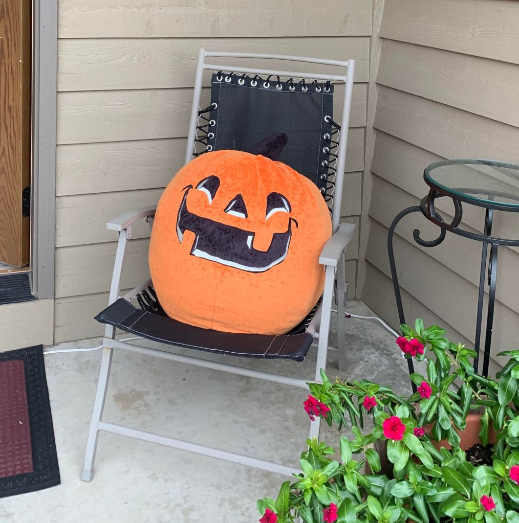 A large orange plush Jack-o-lantern sits on a black folding chair on the front porch, behind a large clay pot full of red flowers.