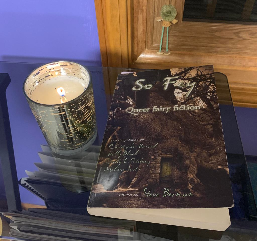 Photo of the book So Fey: Queer fairy fiction, edited by Steve Berman, placed on a glass desk, next to a lit medium-sized candle, seen from slightly above.  The candle is painted on the outside to look like silver birch bark.  The streaks in the silver are transparent, so you can see the glow from the flame.   There's a small faery figure in the left-bottom corner of the window, behind the desk -- it's the only part of the window you can see.  The figure's head is tilted down so their wide-brimmed burlap hat covers their whole face.  They wear a pale orange top with long sleeves, and pale orange shoes.  In between are two long, spindly sea-green legs.