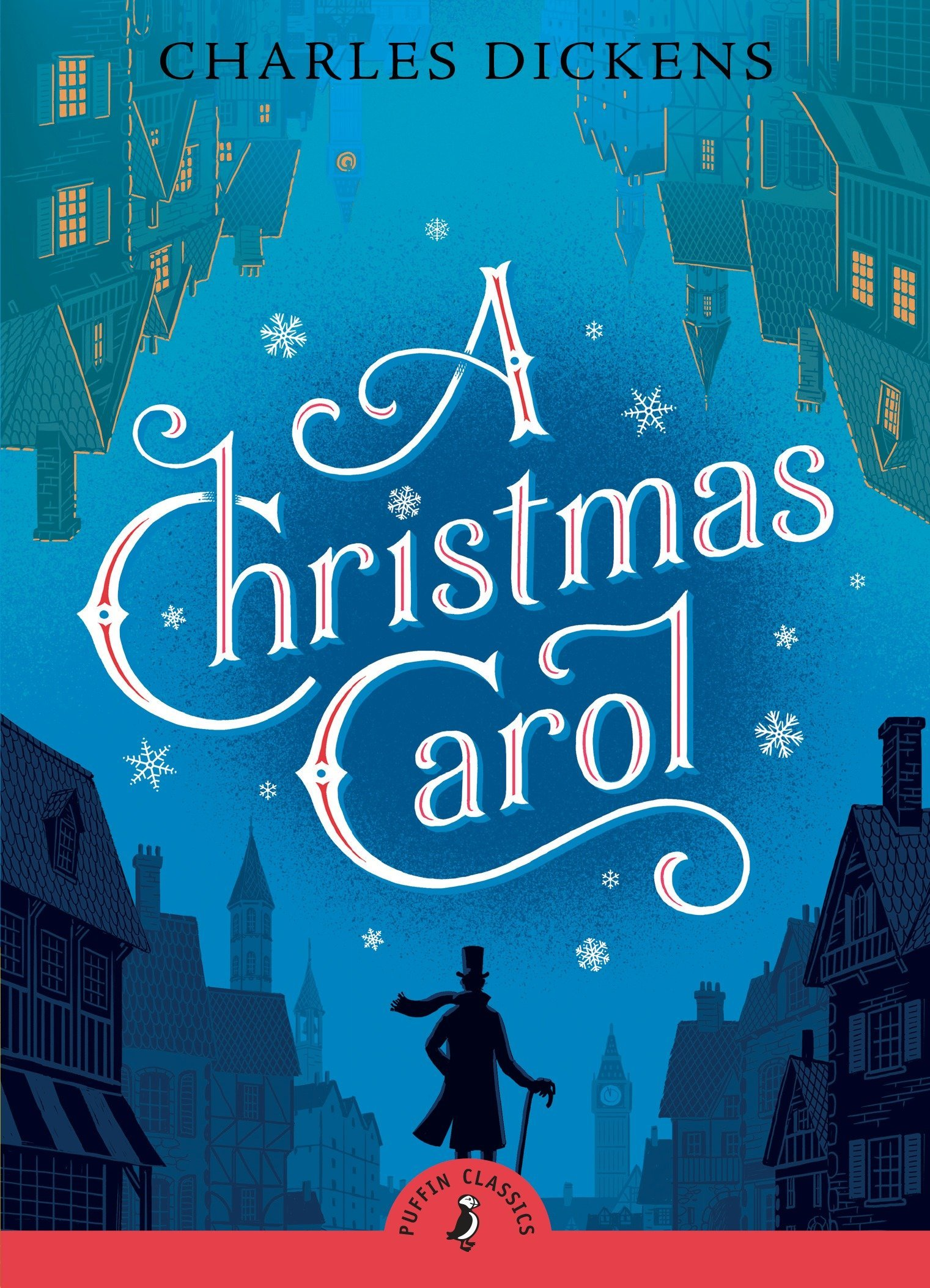 The Puffin Classics cover of A Christmas Carol, by Charles Dickens.  You see a lone silhouette at the bottom, wearing a long coat, a top hat, a flowing scarf, and holding a cane as he walks through a silhouetted Victorian city.  The buildings are arranged in a diamond pattern, bordering the book cover.  On the bottom are the black silhouettes of buildings arranged like staircases going down, meeting at the bottom of the cover.  At the top are green silhouettes of upside-down buildings with lit yellow windows, angled so the bottoms of the buildings meet at the top of the cover.  In the middle of the diamond is a blue night sky covered in snowflakes, as well as the title in large flourished red and white letters.