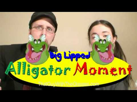 "A screenshot of the Nostalgia Critic and Nostalgia Chick staring at the viewer.  The critic looks weirded out and the Chick looks bored.  In front of them is a big yellow sign, shaped like a long horizontal oval, with the words ""Big Lipped Alligator Moment"" in blue, green, and red.    There are two open-mouthed alligator faces on either side of the words ""Big Lipped.""  Both have ear-like tufts of feathers on their heads and a bone stuck through their noses."