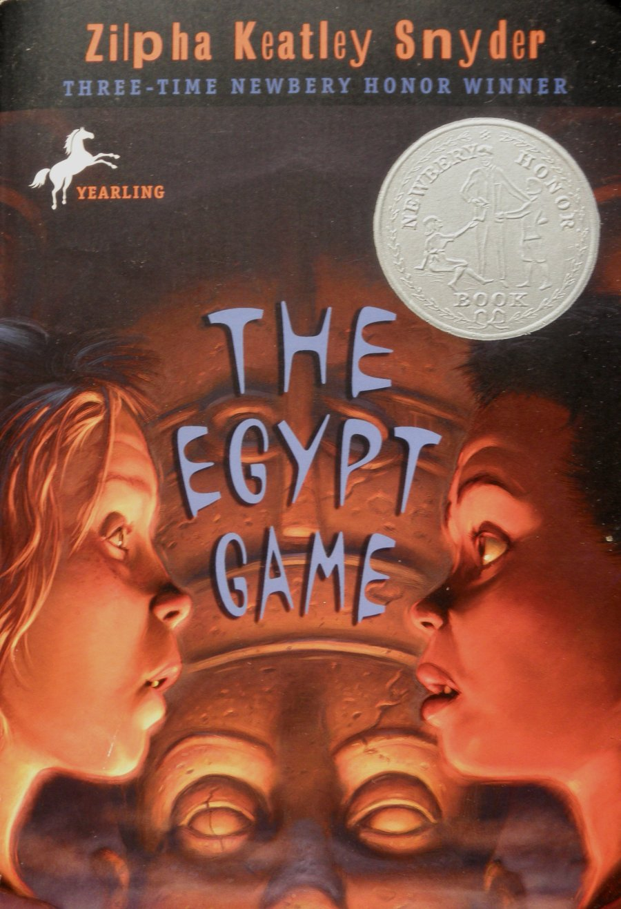 Cover of The Egypt Game, by Zilpha Keatley Snyder.  Two girls stare at each other with wondrous expressions, their faces in profile on opposite sides of the cover.   Between them, you see a statue of an Egyptian queen or pharaoh, their face lit up from below.  The girls' faces are also lit up.  Above them all is darkness.