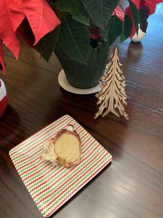 A photo of a slice of bundt cake on a red-and-green-striped paper plate.  The cake is yellow in the center, with white frosting and stripes of ground cloves.  There's a miniature mushroom on top, made from a mini marshmallow and an espresso bean.    Near the plate is a pot of poinsettas and a wooden cut-out of a tall fir tree.