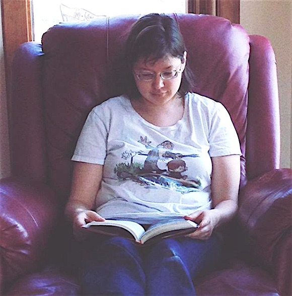Photo of myself sitting on a dark red leather recliner, with a book propped open on my lap.  I have shoulder-length dark brown hair and glasses.  I'm wearing blue jeans and a white t-shirt with a drawing of Gandalf the wizard and Bilbo the hobbit cheerfully walking across a log like Calvin and Hobbes.