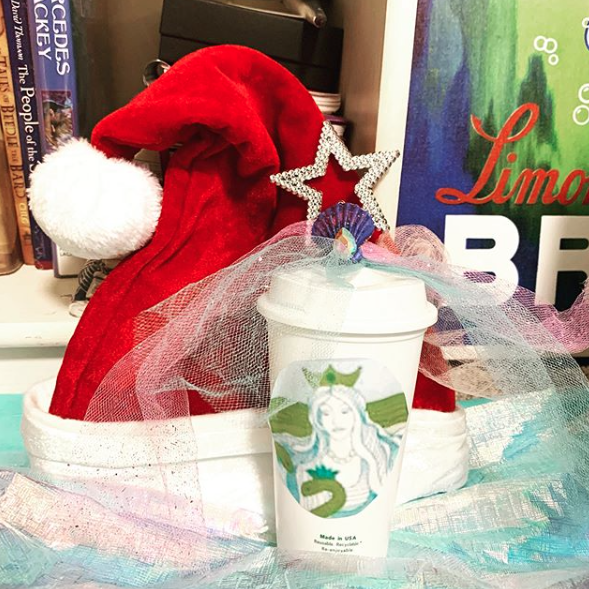 "A photo of a Santa hat standing upright against the bottom-right corner of the bookcase.  In front of the hat is a plastic white coffee cup made to look like a Starbucks paper cup (complete with a lid).  But instead of the Starbucks logo, you see a circular image pasted on, of a scene from the story Egle, Queen of Serpents.    The image is of a woman with long pale hair and a green three-pointed crown.  She's looking down at a snake that has a blue three-pointed crown..  Behind them are green waves.   To the right of the hat and cup is the bottom-left corner of the Limonade Brault poster.  You see dark blue and neon green watercolor streaks and the first few letters of the words ""Limonade"" and ""Brault,"" the former in red and the latter in white."