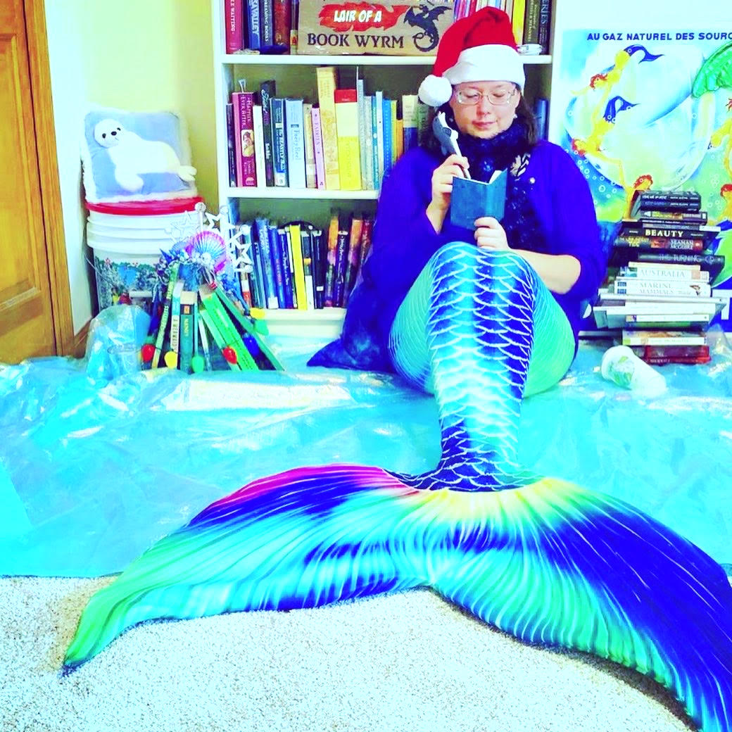 Photo of me in my aurora borealis mermaid tail and Santa hat, with a purple sweater and black scarf with blue and purple accents.  I'm looking down at a small iridescent green notebook in one hand, holding a dolphin-shaped pen in the other.  I'm sitting on a shimmering sheet of icy blue material.  Behind me is a white bookcase.    To my right is a stack of black, white, and red books shaped like a snowman with a top hat and scarf.  Behind that is a copy of the Limonade Brault poster, which shows a chain of six mermaids, holding hands, swimming counter-clockwise out of a wine glass.  To my left is a stack of books standing upright and leaning into each other like a teepee.  It's a Christmas tree, topped with a crown made of plastic blue and pink shells and three silver stars.    The tree is also encircled by a necklace of large multicolored Christmas lights.