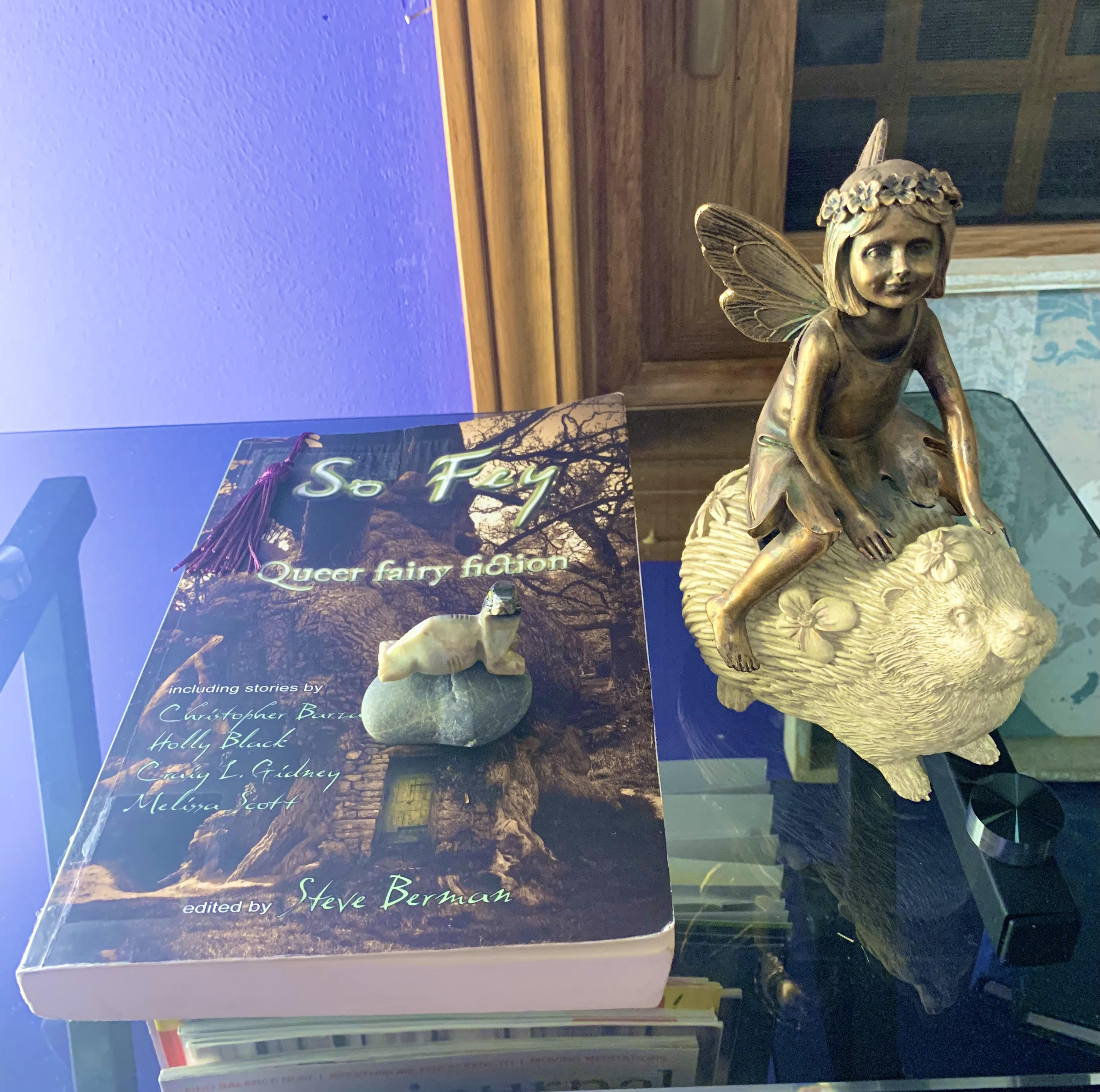 Cover of So Fey: Queer Fairy Fiction, on a glass table.  To the right of the book is a large figurine of a winged fairy child riding a hedgehog covered in flowers.  On top of the book is a small stone with a tiny seal figurine on top.