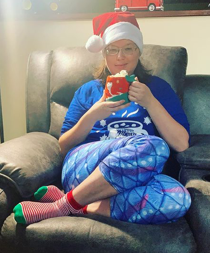 Photo of me wearing a red Santa hat, a dark blue long-sleeved t-shirt with an image of a white hot chocolate mug, a pair of blue capri leggings with a mermaid-scale pattern over purple stripes and several lines of white dots, and a pair of red-and-white-striped socks with green toes.  I'm holding a large mug that looks like a red-haired mermaid, with her curved tail forming the handle.  You can just see a wave of whipped cream peaking up from inside.