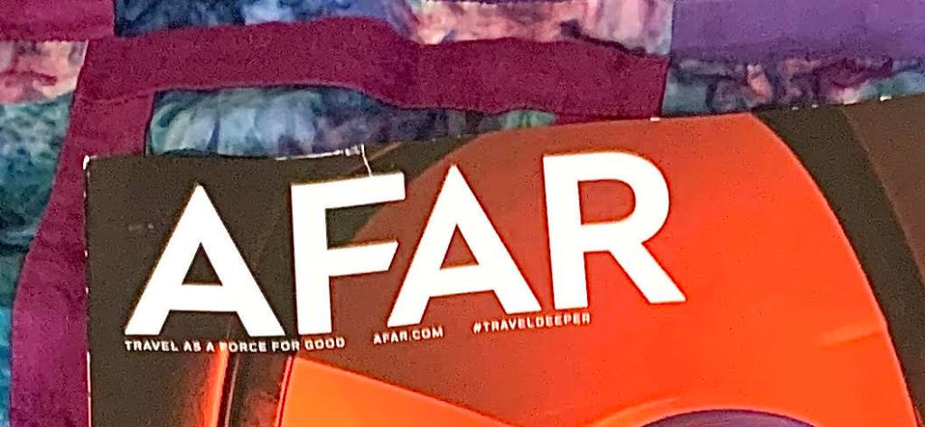 Close up of AFAR magazine.  The title is all caps in white text against a sunset-tinted image of an airplane window from the inside.