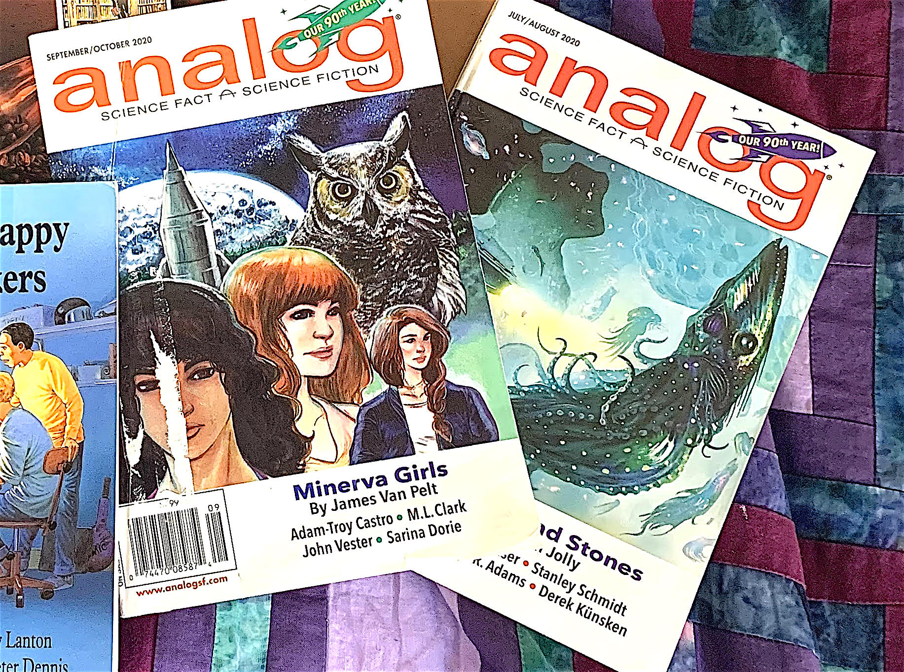 Close up of two issues of analog magazine. One cover shows three women and a large owl in the foreground.  Behind them is a pale moon or planet and a grey rocket pointing straight up.  The other cover shows a giant squid underwater, with the silhouettes of several smaller squid in the background.
