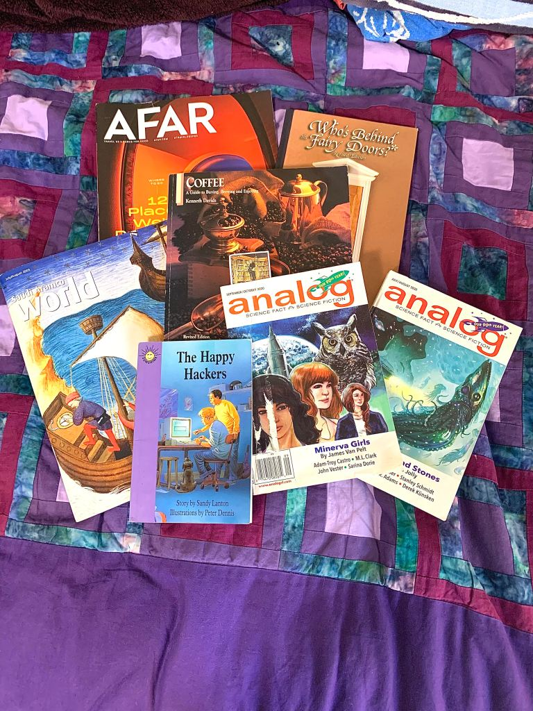 Photo of a pile of books and magazines on a purple quilted bedspread.  The books are described below.