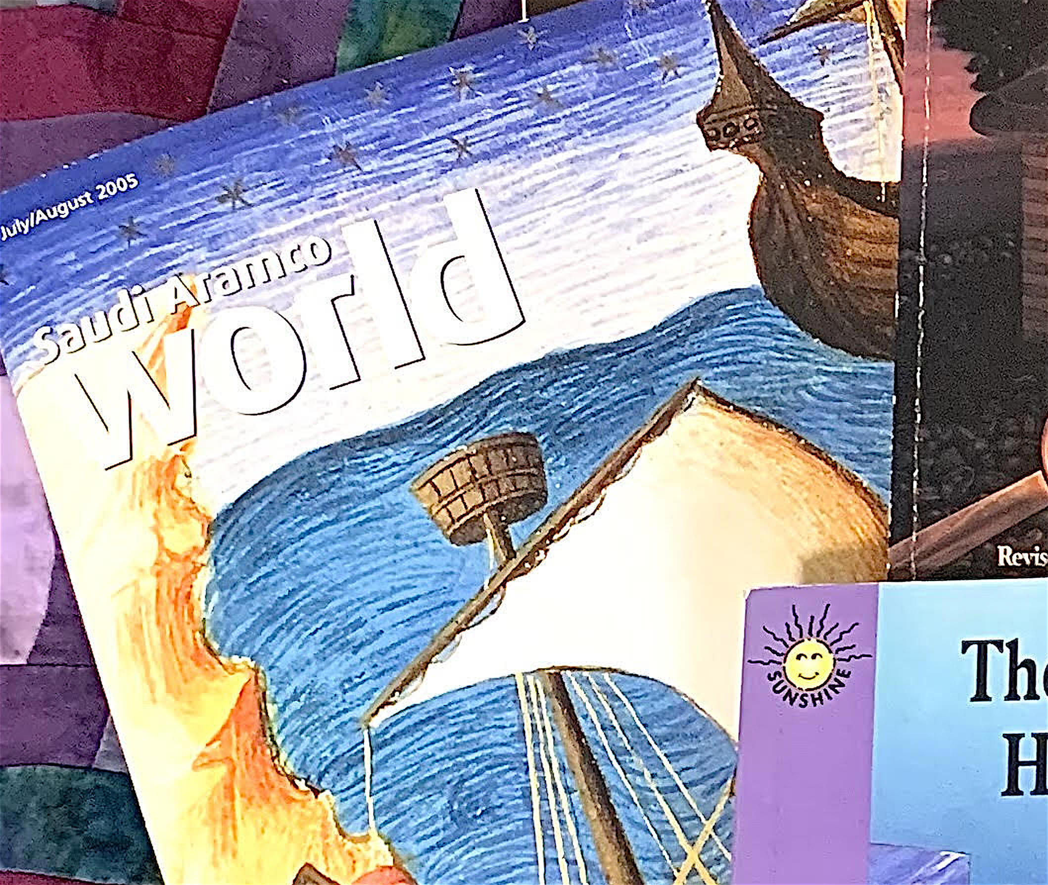 Close-up of Saudi Aramco World magazine.  The cover shows a painting of two ships against a wavy blue sea, each with a large rectangular sail.  There are two sailors on one of the ships -- one is checking a compass and one is climbing the mast.