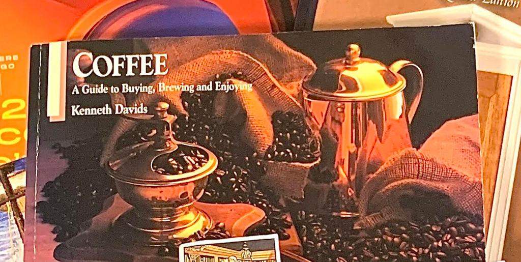 Close-up of Coffee: a Guide to Buying, Brewing, and Enjoying.  The whole cover is a sepia-toned photograph of several burlap sacks of coffee beans, along with an old-fashioned box grinder, a metal coffee pitcher, two metal scoops, and a ceramic coffee-filled cup on a dish.