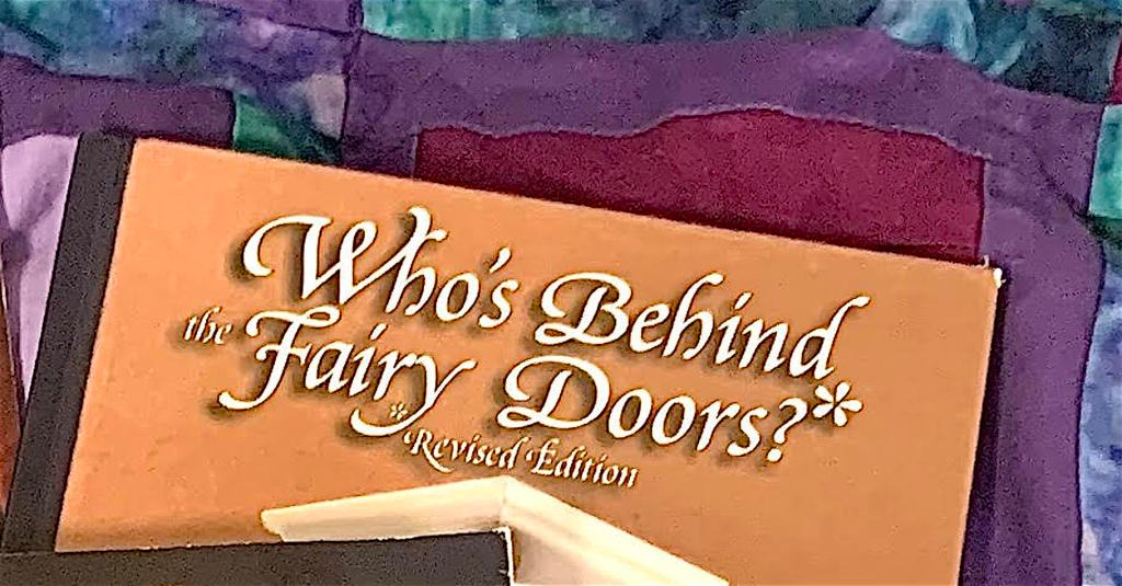 Close-up of Who's Behind the Fairy Doors?  The title is in swooping white script against a dark beige background.  In the center of the cover is a tall door with a white frame and a vertical oval-shaped window.  Through the window, you see a round white ball with beady black eyes and red lips.