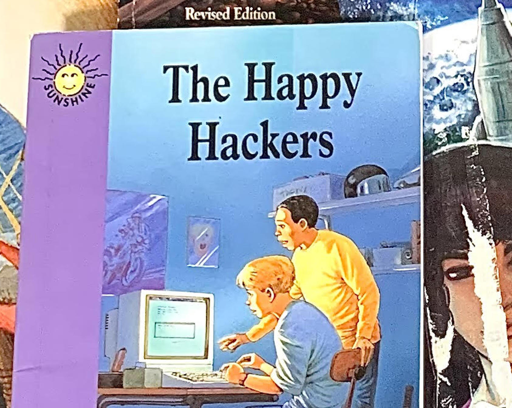 Close-up of The Happy Hackers.  The cover has a vertical violet bar on the left side, with a smiling yellow sun at the top and the word Sunshine curving around the bottom of the sun.  The rest of the cover is a blue-tinted room, as though it's late at night and all the lights except a computer screen are on.  There are two boys staring at an old desktop computer screen, and a scruffy dog staring up at the boys.