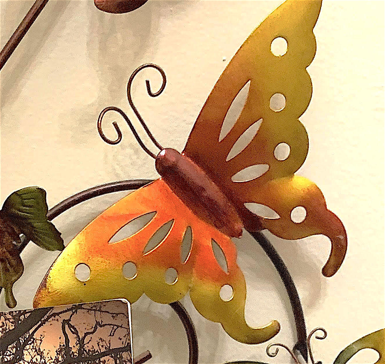 Close-up of one of the metal butterflies.  Its wings are painted bright red-orange at the center and gold on the edges.