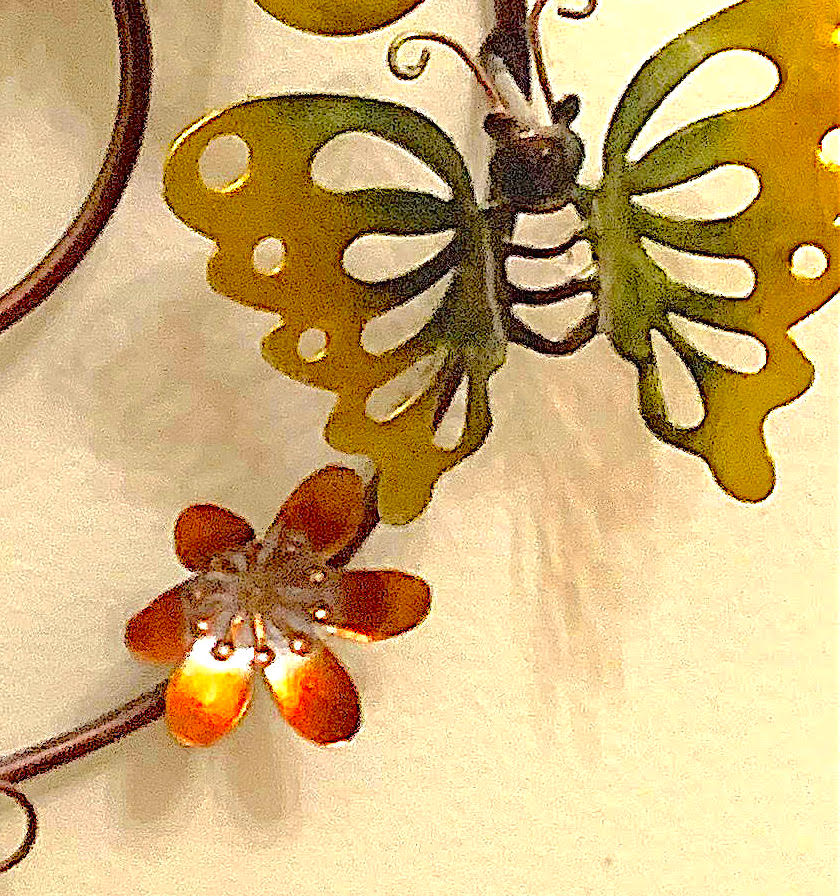 Close-up of a different butterfly with green and gold wings, next to a small red flower.