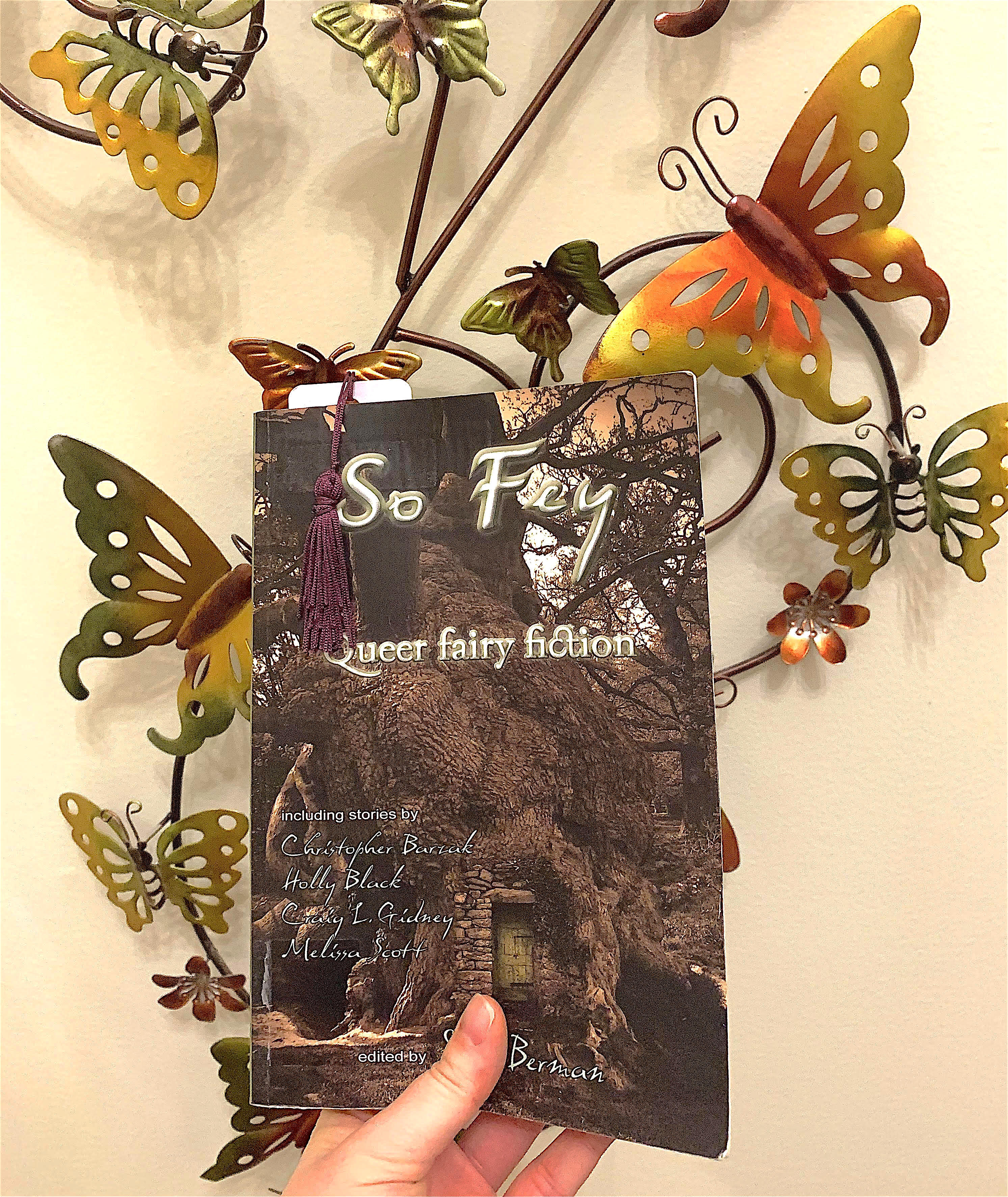 My hand is holding So Fey Queer Fairy Fiction, by Steve Berman, in front of a wall hanging made of metal butterflies in shades of red, gold, and green.