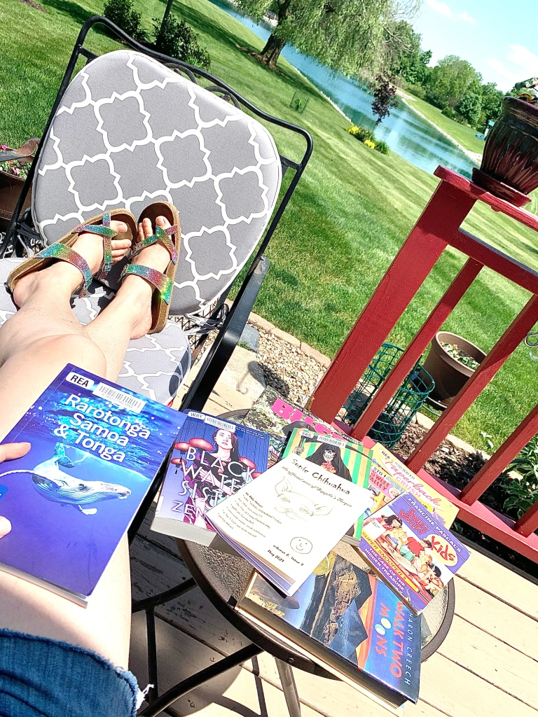 A photo of me chilling on the back porch, facing the lake on a sunny day.  You only see my legs and feet stretched out onto a chair.  I'm wearing sparkly rainbow sandals and holding a Lonely Planet guide to Rarotonga, Samoa, and Tonga.  On a small table next to me is a pile of books and such.  You can just make out fragments of titles like BU??, BLACK WATE SIST, SONIC CHIHUAHUA, PAPERBACK CRUSH, a few Sweet Valley Kids books, and WALK TWO MOONS.