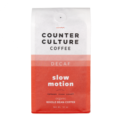 Image of a bag of Slow Motion coffee.  The bag is white on top, with the company name in black, and orange on the bottom, with the words slow motion in white.