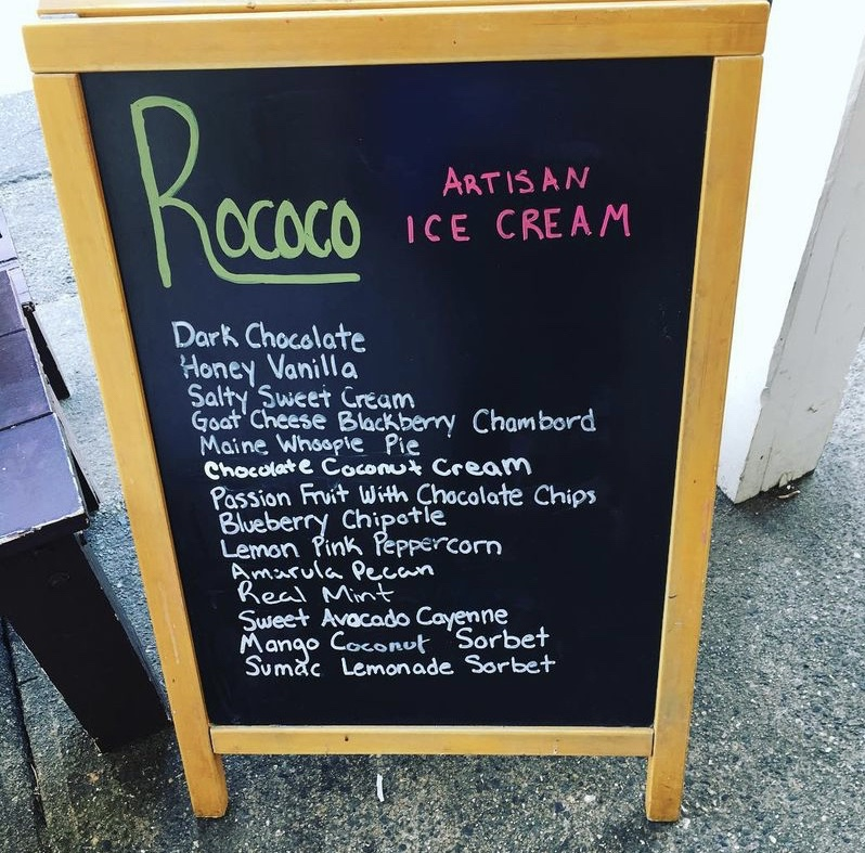 Photo of a sandwich board outside Rococo's Artisan Ice Cream, listing their flavors of the day.  There's dark chocolate, honey vanilla, salty sweet cream, goat cheese blackberry chambord, maine whoopie pie, chocolate coconut cream, passion fruit with chocolate chips, blueberry chipotle, lemon pink peppercorn, amarula pecan, real mint, sweet avocado cayenne, mango coconut sorbet, and sumac lemonade sorbet.