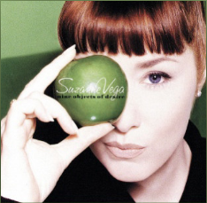 Image of a Suzanne Vega album cover showing a pale face with straight-cut red bangs and a pale hand holding a green apple over her right eye.
