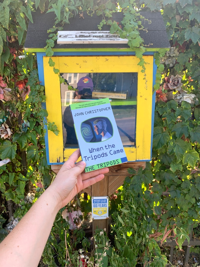 Photo of a Little Free Library box in front of a gate covered over with ivy.  The box is blue with a yellow-framed door.  A hand holds up a silver and green paperback in front of the window.  The book is When the Tripods Came, and the cover has a window in the center, shaped like a rounded TV screen, through which you see a person wearing a form-fitting blue helmet and staring at a TV screen that literally shows a giant hypnosis wheel with bright green and dark blue swirls.