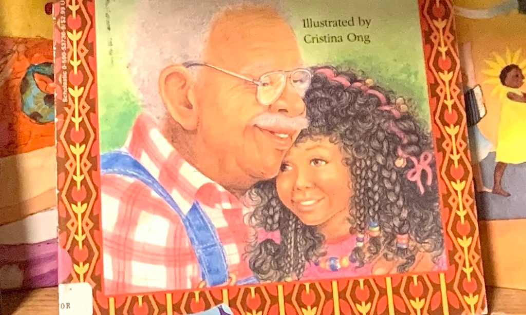 Cover of Kenya's Family Reunion.  A girl hugs her grandfather, both of them smiling brightly.  The girl has dark curly hair filled with lots of pink bows. Her grandfather wears glasses and a red and white plaid shirt with blue denim overalls.