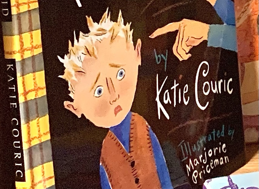 Cover of The Brand New Kid.  A boy with pale skin and spiky blond hair looks very worried as his new teacher points to him in front of a blackboard.