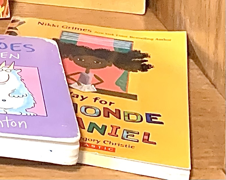 Cover of Make Way For Dyamonde Daniel.  You see a little girl looking out through a window, propping a math book open on the windowsill.  She has curly black hair that sticks straight out on either side of her head.  She wears a purple sleeveless top and her name is written in big dancing letters against a bright yellow background, each one a different color.