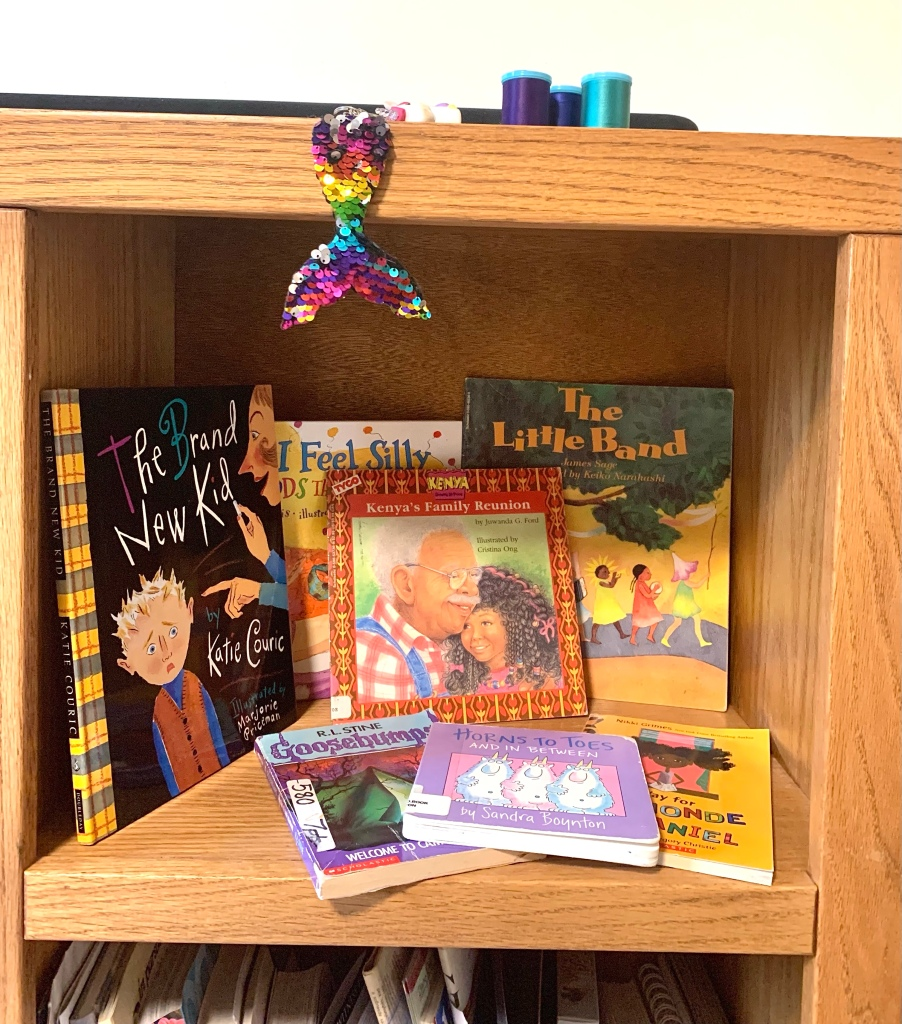 Square cubby, part of a free-standing shelf unit, with picture book display inside, along with two chapter books and a board book.  A rainbow mermaid tail keychain hangs down from the top of the shelf unit.